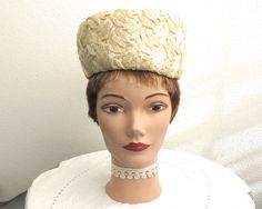 Vintage cream pillbox hat, 1960s, cellophane straw with floral decoration at the back in dark cream chiffon fabric, hat sits on top of head by…