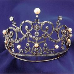 Circa 1900 diamond and natural pearl belle epoque tiara designed as a series of garlands and foliate scrolls, encompassing many pink button natural pearls and 620 old European cut diamonds, and raised on a diamond band.