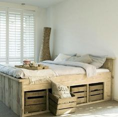 DIY Bed Frame with Crate Storage Repurpose wooden crates as storage for linens, extra pillows, and items that would otherwise be littering your night table.