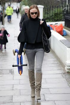 Stella McCartney Photos Photos - Stella McCartney carries her son's scooter as she walks home after doing the morning school run. The designer daughter of Sir Paul McCartney and his late wife, Linda, was wearing a knee high pair of boots, grey jeans and a black sweater. - Stella McCartney Carries a Scooter