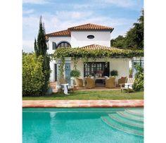 A casa, que lembra uma vila na Toscana, tijolos de tom terroso formam a borda desta piscina de águas azul claras