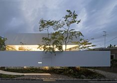 A narrow white wall appears to hover around the perimeter and garden of this house and atelier.