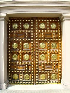 A large door, decorated with brass plates, on Passeig de Colom, Barcelona, Spain (=)