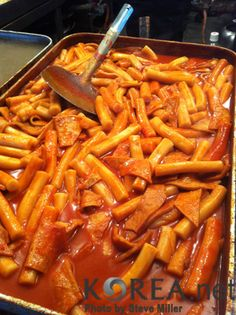 Ddeokbokki - cylindrical rice cakes cooked in a chili paste with pieces of fish cake (South Korea)