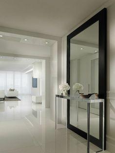 decoration hall de maison au sol au carrelage brillant et au grand miroir au cadre noir et une table haute en métal blanc