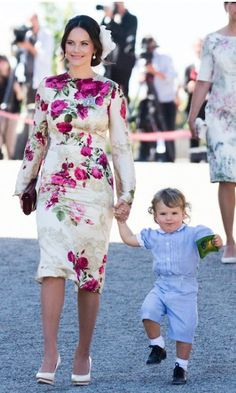 Princess Sofia dazzles in a pink and cream floral dress as she arrives to the ceremony with her eldest son Prince Alexander, 2. Here, the adorable toddler skips alongside his mother wearing a blue one-piece from his father's closet. Prince Carl Philip was pictured wearing the garment back in 1982. Photo © Samir Hussein/WireImage
