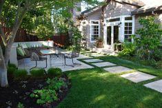 kleine Terrasse mit Fliesen verlegt und Trittplatten im Rasen