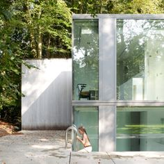 """Residential Architecture: Villa Roces by Govaert & Vanhoutte: """"..This glass house..has a 50-metre-long wall at the back and a sunken swimming pool at the front..the house is long and narrow and contains staggered storeys that descend below the ground..The swimming pool is located at the lowest level and is tucked into a recessed corner of the building.Inside, a long ramp slopes up from the main living and dining room towards children's bedrooms that are half a storey above…"""