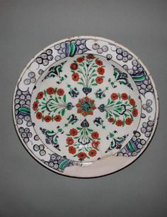 Fitzwilliam Museum Collections (Id:75542)...Iznik dish Date: circa 1565 — 1585 fritware with white slip painted in red, blue, black and green under a clear glaze fritware coated in a white slip painted with red slip and blue, black and green pigment under a clear glaze. Shape: segmental bowl with slightly angled plain rim sitting on a low, wide foot ring