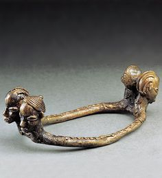 Burkina Faso  Bronze   Late 18th century  Length 17cm   Anklets of this oval-shaped are characteristic of the savanna region of southwest Burkina Faso. The remarkable brass piece is made from lost-wax casting, decorated with depictions of the four heads of the ancestors. Wearing jewellery in the image of the ancestors is considered to elicit their power and protection and to aid communication between living and dead