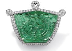 A carved emerald and diamond brooch/pendant. The shield-shaped emerald, weighing approximately 135.00 carats, carved with foliate details to front and back and set within a brilliant-cut diamond looped frame, length 4.6 cm, multiple concealed pendant attachments, double pin fitting.