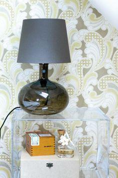 Det gjennomsiktige nattbordet Ghost Buster er fra Kartell, og kan kjøpes fra nettbutikken room21.no. Bordlampen er fra Ikea.