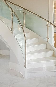 Modern curved staircase with stainless steel and glass railings for clean, clear views. Staircase Glass Design, Balcony Glass Design, Staircase Design Modern, Steel Railing Design, Modern Stair Railing, Staircase Handrail, Balcony Railing Design, Home Stairs Design, Glass Stairs
