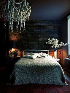 Love this cozy room, black shade creates pool of light, large beaded chandelier, nubby bedspread, large red rug, log wall Via: Abigail Ahern