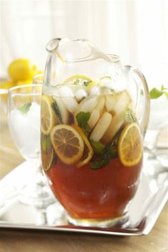 Mint Julep Tea. Made with mint simple syrup (sugar, water, and mint leaves), lemon slices, lime slices, bourbon, unsweetened tea, cubed ice, and mint.