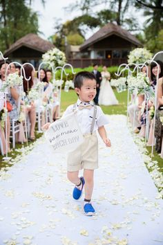 "Page boy holding Love you more each day sign on wedding aisle // Wedding Boutique Phuket dreamt up a vintage European ""Key of Love""-inspired celebration on the beachfront lawn of Renaissance Phuket Resort & Spa, Thailand, for David and Ivy. Captured by Darinimages, this wedding theme came complete with vintage key motifs, shades of Rose Quartz and Serenity Blue, and a vintage door ceremony backdrop opening out into the sea."
