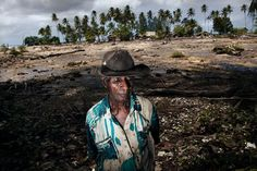 Posakei Pongap, a Manus islander, in front of a field ruined by salinization. Photo courtesy Conversations with the Earth/Nicolas Villaume.