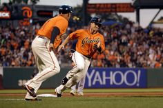 Third base coach Tim Flannery runs along side Buster Posey of the San Francisco Giants as Posey rounds third base on his way to scoring on a hit by Pablo Sandoval in the first inning of their game against the Milwaukee Brewers at AT&T Park on August 29, 2014 in San Francisco, California.