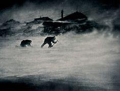 Due uomini nella tormenta raccolgono ghiaccio, fonte di acqua potabile: un'operazione quotidiana durante la spedizione scientifica in Antartide (dal 1911 al 1914) sponsorizzata dall'Australia.