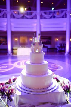 Classic three-tier white wedding cake with Cinderella Castle cake topper at a Walt Disney World reception