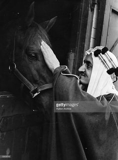 Faisal ibn Abdul Aziz, (1906 - 1975), Crown Prince of Saudi Arabia, strokes a horse at the Royal Stables.