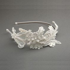 The Javier Lace Bridal Headband is Ivory and is created out of high quality antique lace and is adorned with dainty pearls and sequins. The headband is created for an adults head size.Measurement: The lace on the band spans 24cm across the headband and is 8.9cm at its widest point. The satin covered headband is thin at .037cm wide.Presented in Roman