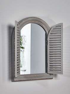 With a painted grey distressed frame, our traditional style shutter window mirror is reminiscent of traditional French windows, and will add a touch of rustic chic to your interior. Made from paulownia wood, it has two hinged, slatted shutters and an attractive, arched shape. Perfect for a kitchen or conservatory.