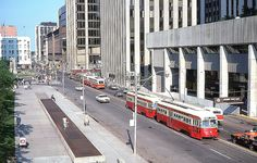 76-July a Queen streetcar in rush hour. To the left- city hall. On the right- Sheraton Centre. Down the street-EATON'S and SIMPSON's