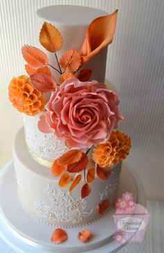 """Autumnal wedding cake with giant sugar rose, dahlias and calla lily, and leaf sprays inspired by the invitations. Gilded lace brush embroidery inspired by the bride's Berketex """"Piper"""" wedding dress."""
