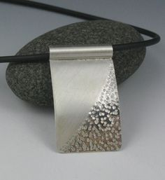 Silver Zen Rectangular Pendant on Rubber Cord This rectangular pendant has a combination of textures. The sand texture is inspired by the raked sand gardens often seen in Japanese gardens. Each grain of sand has been hand stamped into the metal. The sand area of the pendant has a high polish, while the other part has a matte finish. The pendant is slightly curved from top to bottom to create more dimension. Pendant measures 1w (2.5cm) x 1 1/2L (3.9cm) Price includes a 16 black rubber cord…