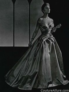 Jean Patou designed this silk satin ballgown in 1954.  The voluminous skirt is gathered into a buckle at the waist.  Via Couture Allure.