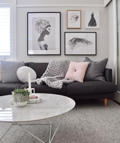 Living room art print arrangement above the couch / sofa in the living room. Grey, monochromatic and blush colour scheme.