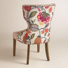 With a curvy keyhole silhouette and a pop of bold color, our dining chair brings bright style to the table. Upholstered with natural tufted linen on one side and an oversized floral print on the back, it's framed with nail heads for a classic touch.