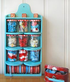 aqua shelf with empty Bon Maman jam jars - the ones with the adorable red gingham lids - to hold trims and embellishments