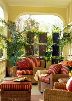 Love the red cushions on the wicker furniture, mixed with yellow color and tall green plants.... beautiful porch.