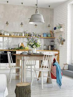 W jadalni drewniany okrągły stół i białe krzesła.