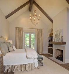 The master bedroom is a retreat of its own with a vaulted ceiling and cozy fireplace. Lower cabinets and shelves are replaced with reclaimed wood for a more custom approach to the cavernous spaces. Lighting by Circa, bedding by Cindy Witmer Designs and Kuhl Linscomb. Linda Falk draperies.