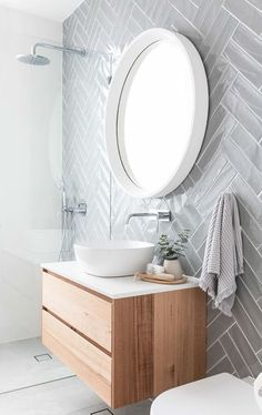 Grey herringbone subway tile on modern bathroom with floating vanity, white vessel sink and round mirror