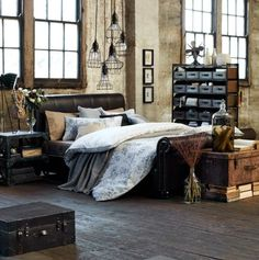 quarto com decoração estilo industrial com elementos vintage, malas antigas, paredes rústicas, cabeceira de couro marrom