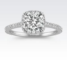Sweep her off her feet with this gorgeous halo engagement ring. With 58 round pavé-set diamonds, at approximately .42 karat total weight, this ring awaits your choice of a 1.25 carat center cushion cut diamond.  The 1.5mm ring is crafted from quality 14 karat white gold.
