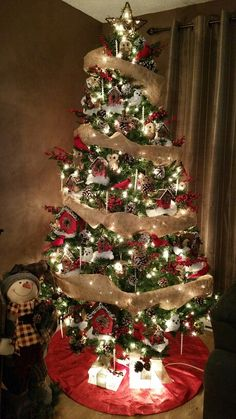 Christmas tree decorated in red, white and brown coloured decorations! Burlap ribbon, holly berries, pinecones, bird houses, birds and squirrels