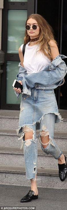 Jean-ius: The model wore a light jean jacket pulled midway down her arms and teamed it with torn jeans which emerged from underneath a ripped skirt