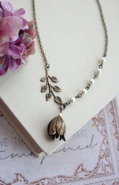 Une fleur de pétale tulipe laiton oxydé beau style vintage. Il est jumelé avec perles swarovski Ivoire. De lautre côté est une branche de feuilles de