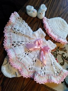 White and pink crochet baby dress set.                                                                                                                                                                                 More