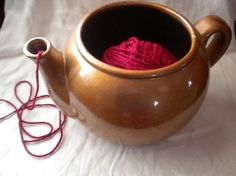 A tea kettle will also keep your yarn from rolling away. What a great way to re-purpose an old tea pot!