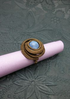Blue fire agate stone wrapped in antique brass colored copper wire. A bit larger than a size 8.
