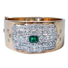 This is a beautiful and elegant 1940's 14 Karat Yellow Gold Bangle Bracelet, inset with an original Art Deco Platinum, Diamond and Emerald Plaque, circa 1920. The bangle is sprinkled with three round diamonds engraved with a starburst on each side of the diamond plaque. The diamonds are of old European Cut and weigh a total of approximately 8.0 Carats.The emerald weighs approximately 1.20 Carats and is emerald cut. Interior Diameter: 7 Inches.