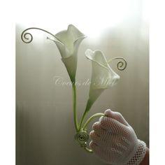 Nature et élégant, ce porte alliance sera idéal pour un mariage au thème arum et fleurs. Réalisé à partir de deux fleurs calla, ce coussin d'alliance est orné de spirales en fil. Vous pourrez y maintenir vos alliances grâce aux arabesques.