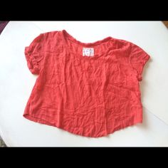 """Free people crop top shirt orange m short sleeve This is a beautiful crop top by Free People. It has a crew neck with beautiful fraying for a distressed look. It is short sleeves, is very light and airy, and is an oversized fit. It feels like linen but is a rayon, cotton blend. It is a size M. Hand wash, dry flat. Has run across the front on one side, see photo. Also lightly pilled/fuzzed.  Shoulder to shoulder: 21"""" Arm pit to arm pit: 22.5"""" Waist: 22.5"""" Shoulder to hem: 18"""" at shortest…"""