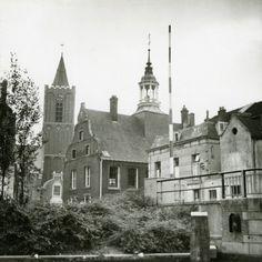Datering tot: 1958-12-31 Beschrijving: De Ooievaarssteeg gezien vanaf de overzijde van de Schie langs de zijkant van de brug in de richting van de achterzijde van het stadhuis en de toren van de Grote of St.Janskerk.